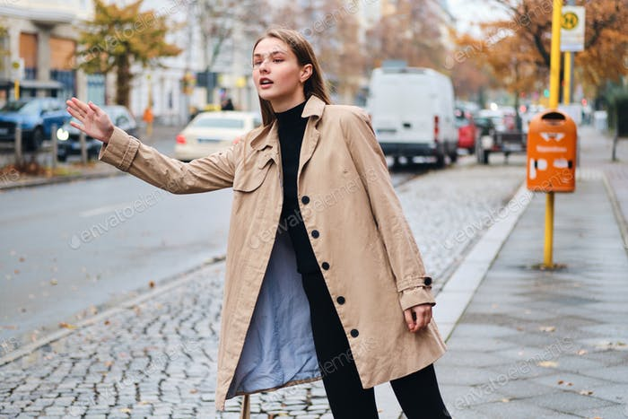 Beautiful stylish girl in trench coat thoughtfully catching taxi on street