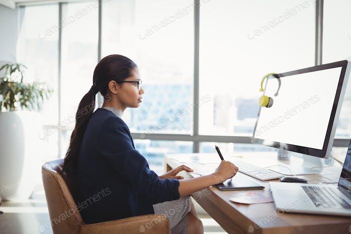 Attentive graphic designer working at desk