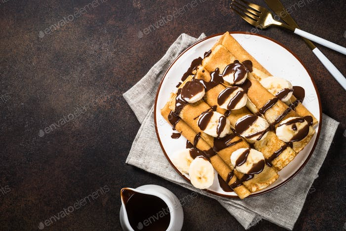 Crepes with chocolate and banana top view