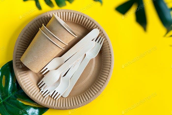 Umweltfreundliches Einweggeschirr aus Papier und Holz auf gelbem Hintergrund mit Grün