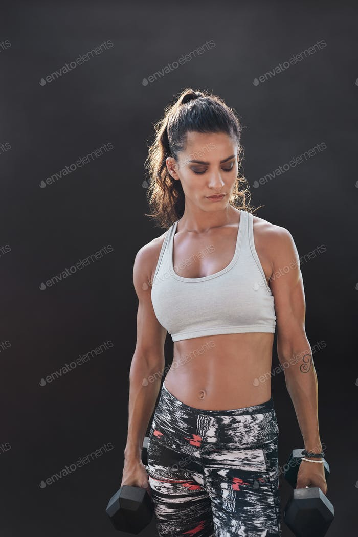 Fitness model exercising with dumbbells