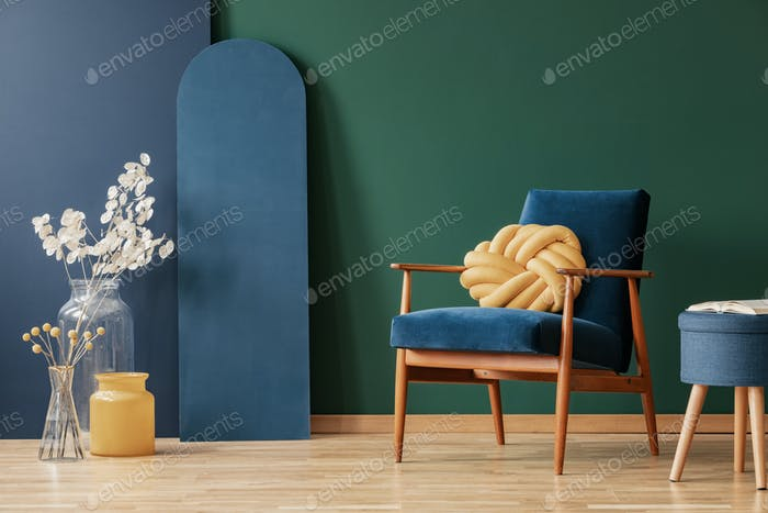 Yellow pillow on wooden armchair in blue and green flat interior with flowers and stool. Real photo