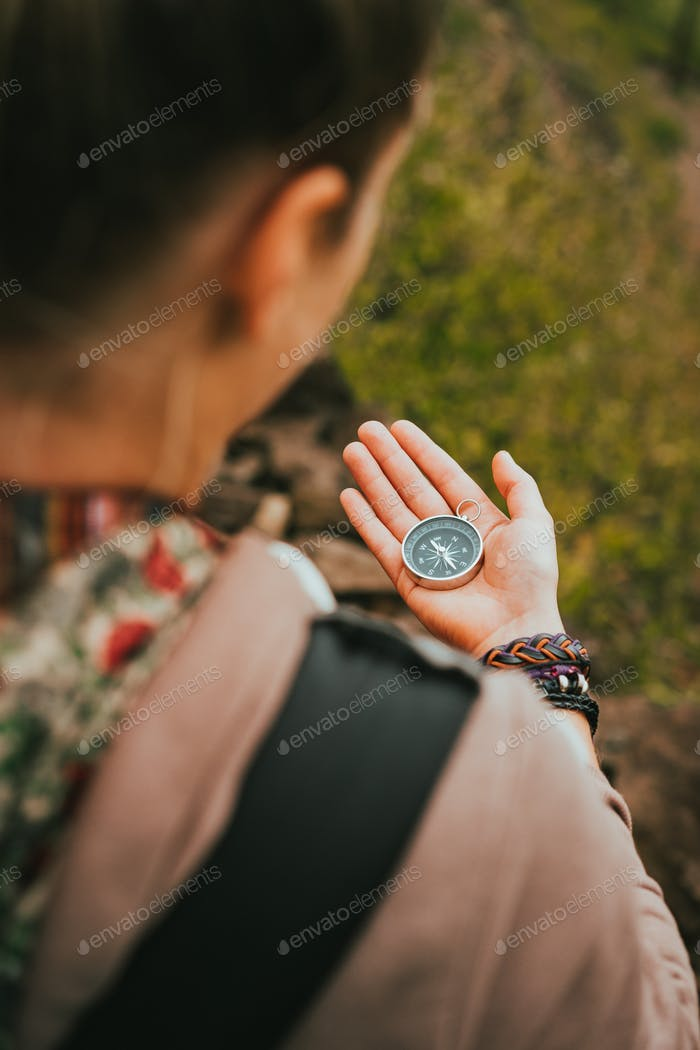 Women check direction at the compass in her hand to find right hiking path