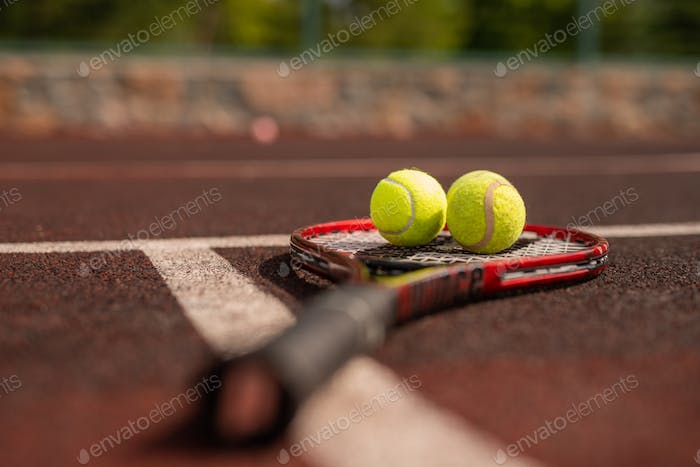 Two balls for playing tennis on racket crossing white line