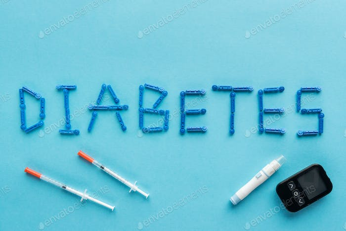diabetes word with syringes and medical equipment on blue background