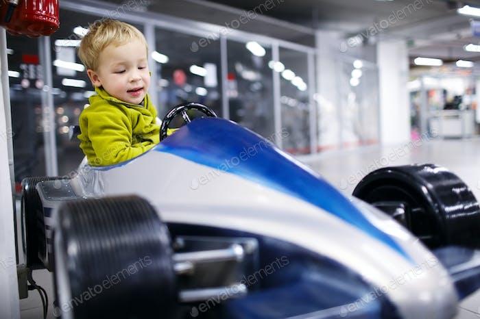Little boy driving a racing car