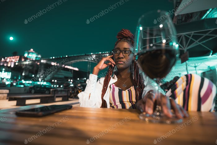 Night cafe with black girl and wine