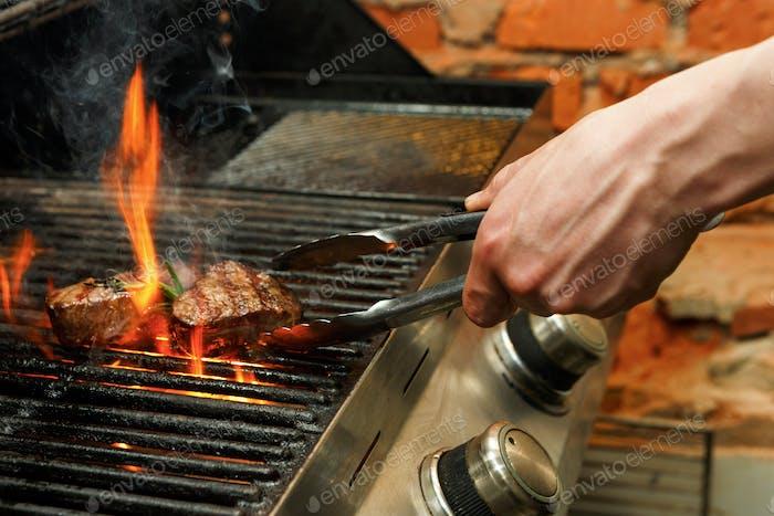 Mann Kochen Fleisch Steaks auf professionellen Grill im Freien