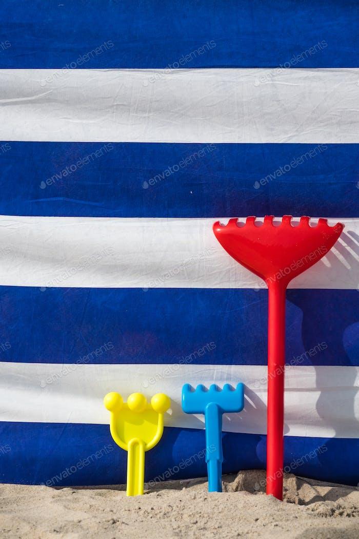 Bunte Kinder Strand Spielzeug in einem Sand vor einem Wind Geröll