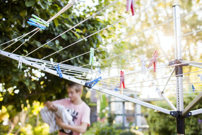 Clothespins hanging on clothesline with boy in background at backyard