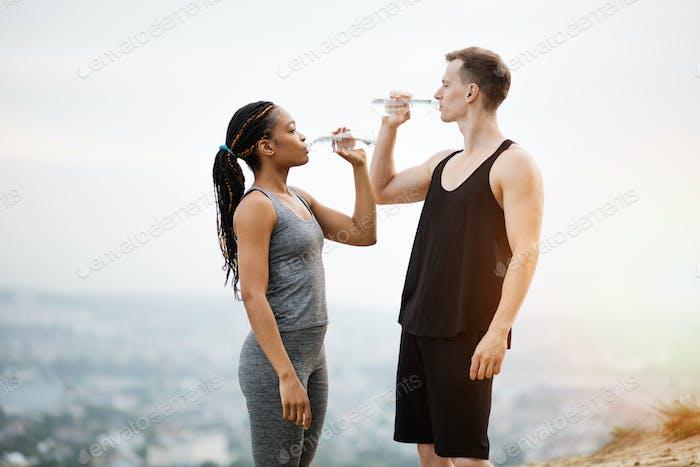 Pareja multirracial bebiendo agua después de actividad al aire libre