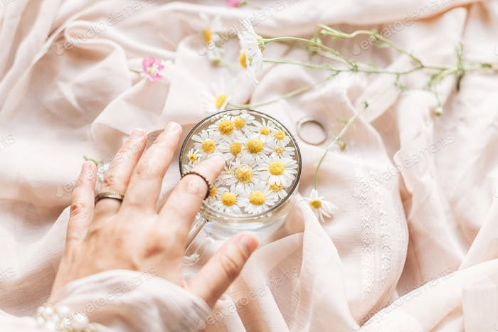 Hand with jewelry holding glass cup with daisy flowers