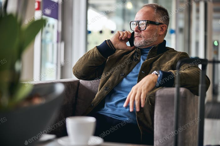 Grey-haired Caucasian man making a phone call