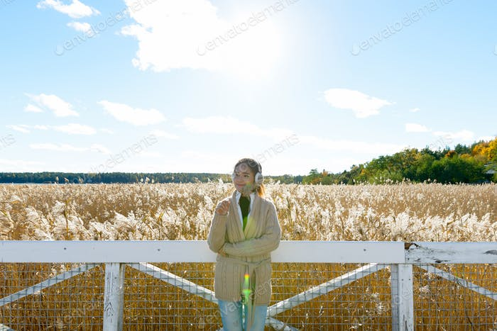 Young beautiful Asian woman holding grass while thinking against scenic view of autumn bulrush field