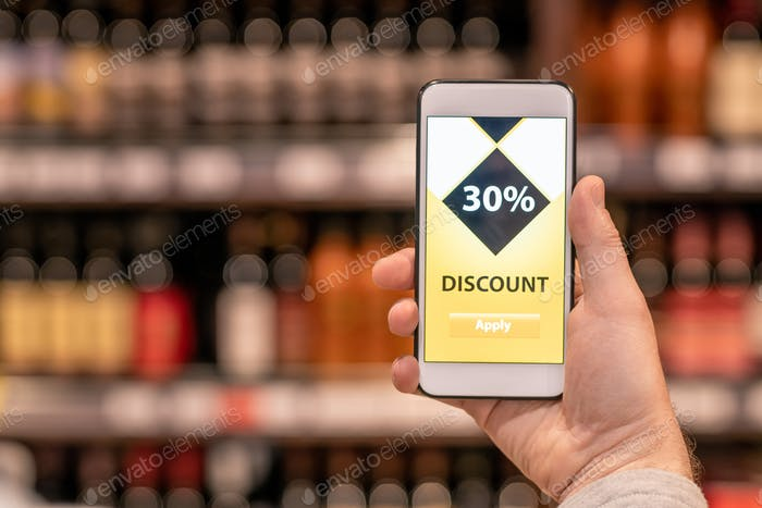 Hand of mobile mature customer holding smartphone with discount application