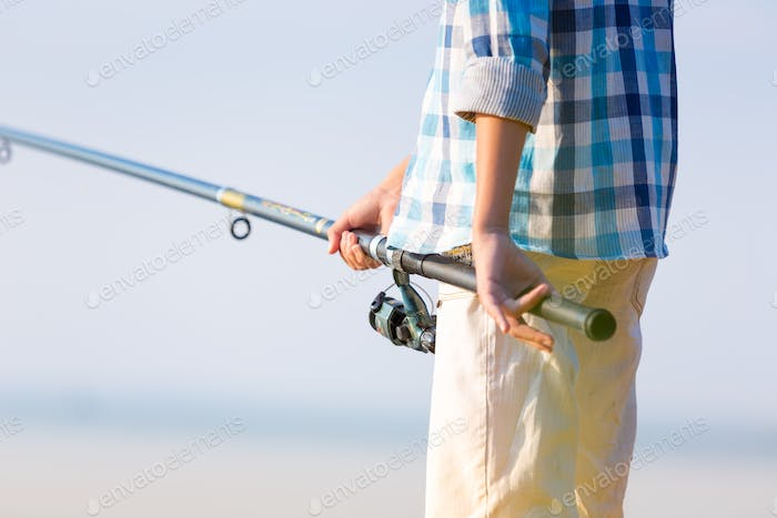 Boy with fishing rod saty on a pier