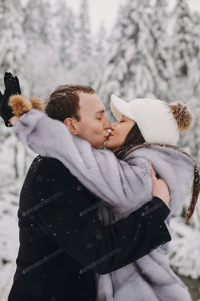 Stylish couple kissing in winter snowy mountains