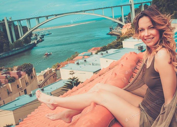 Женщина наслаждается загорать на крыше, на фоне речного моста.