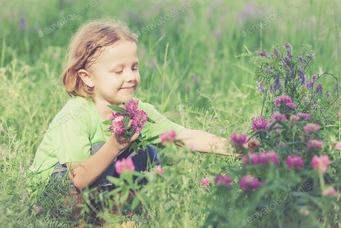Cute little boy  playing with flowers in  park