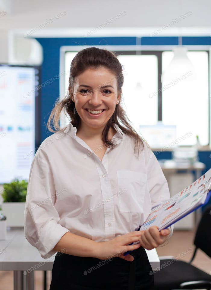 Project manager looking at camera smiling, standing in middle of conference room