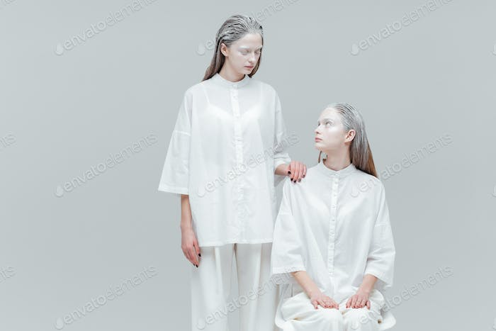 Two women looking at each other in white clothes