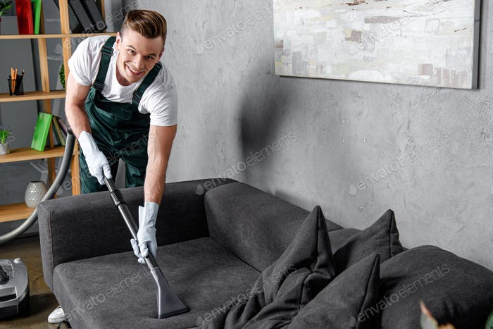 handsome young man in rubber gloves cleaning furniture and smiling at camera