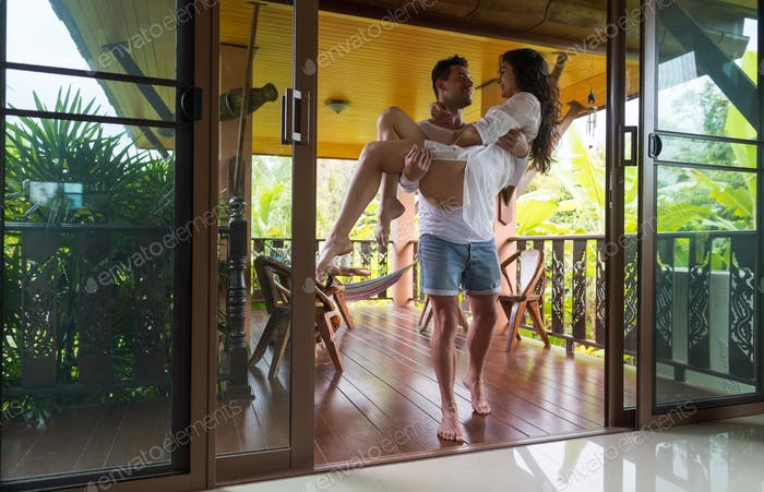 Man Holding Woman On His Hands Enter Home From Summer Terrace, Young Couple Lovers Happy Smiling