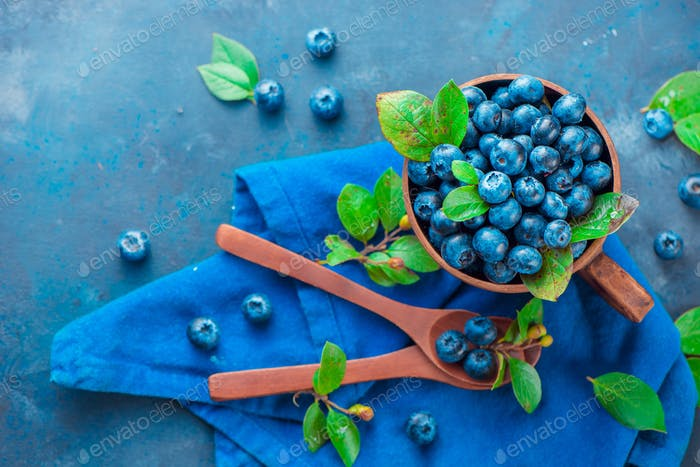 Summer berries flat lay. Blueberries in a ceramic cup with wooden spoons from above. Neutral colors
