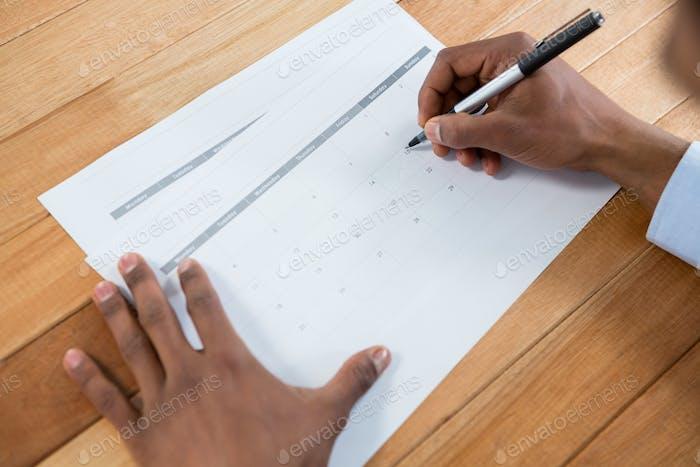 Geschäftsmann Markierung mit Stift auf Kalender