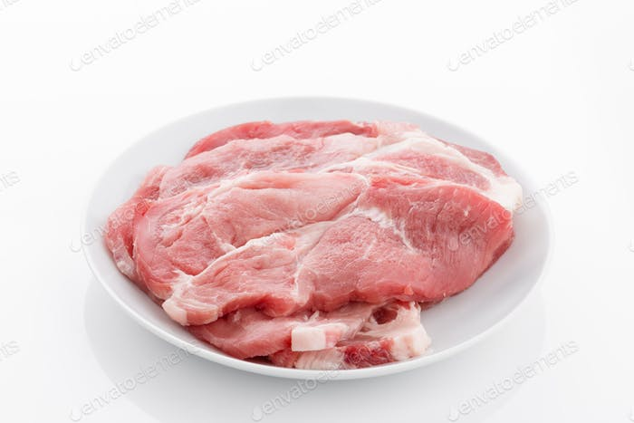 lean pork steaks on plate isolated on white