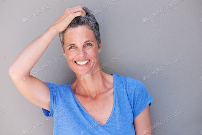 Close up happy woman laughing with hand in hair
