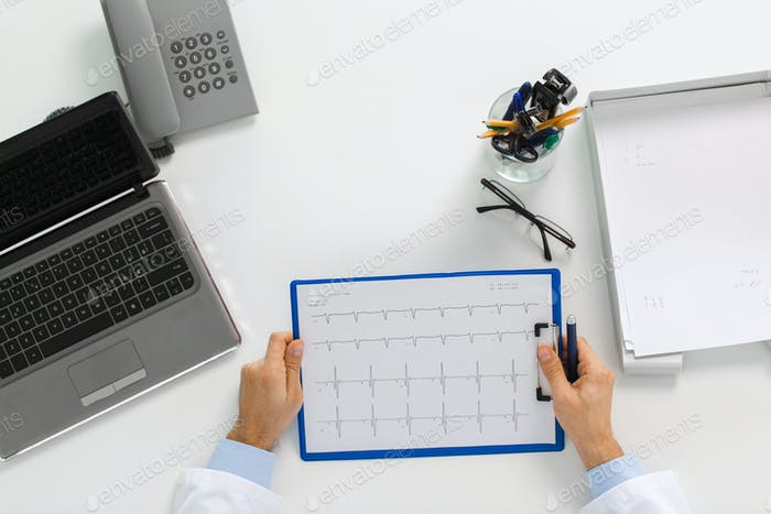 doctor hands with cardiogram and laptop at clinic