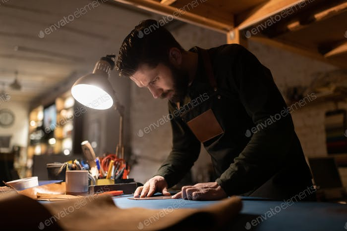 Serious man working with leather