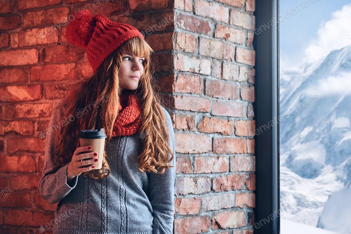 A woman holds coffee and looking over the window on a winter mountain.