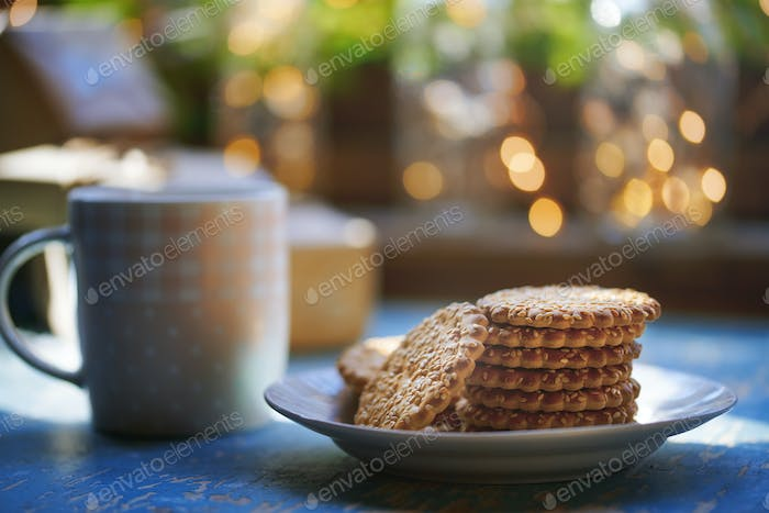 Teacup and Christmas gluten free cookies on a table near the window