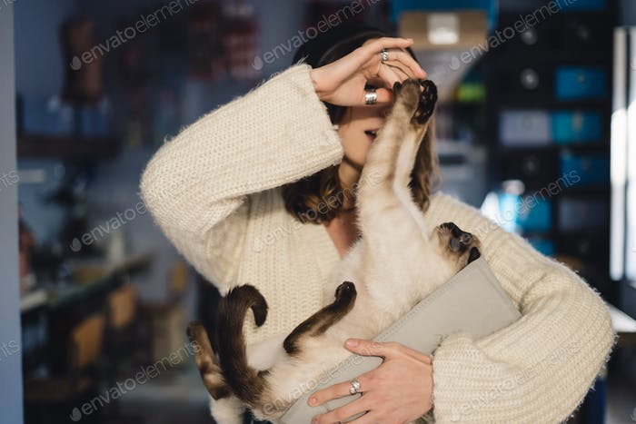 Cheerful woman spends time with her cat