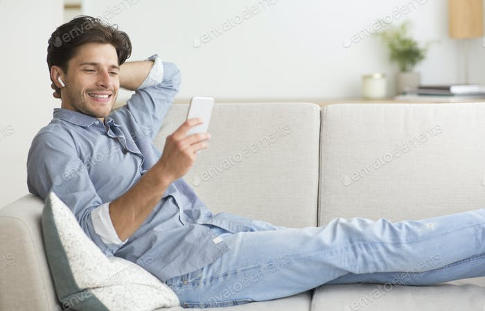 Man Using Smartphone Listening To Music Lying On Sofa Indoor