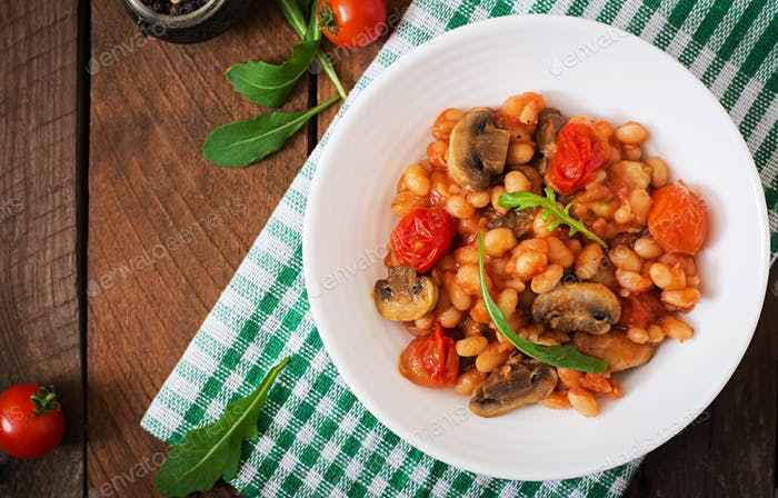 Stewed white beans with mushrooms and tomatoes with spicy sauce in a white bowl. Top view