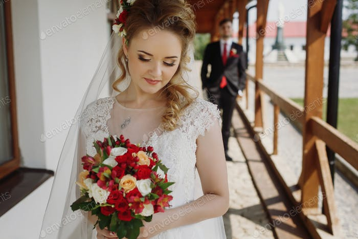 Hermosa novia rubia posando con ramo