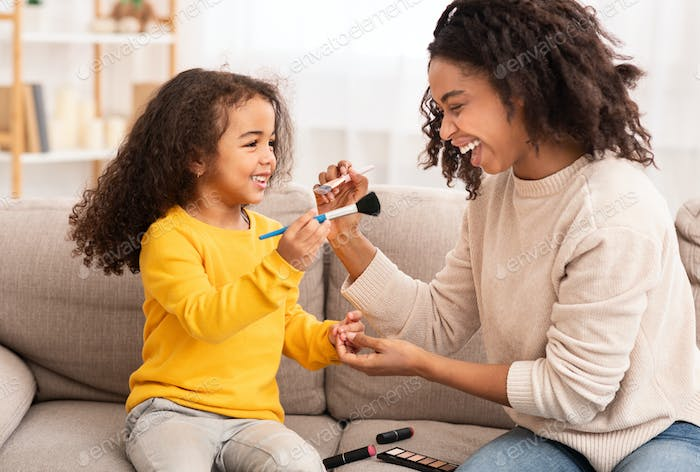 Cute Little Girl And Her Mother Making Makeup At Home