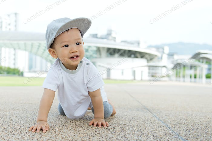 Asian baby boy crawling in park