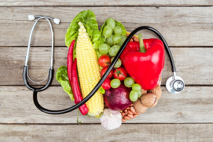 Draufsicht von Stethoskop, verschiedene Bio-Gemüse und Obst auf Holzoberfläche, sauberes Essen