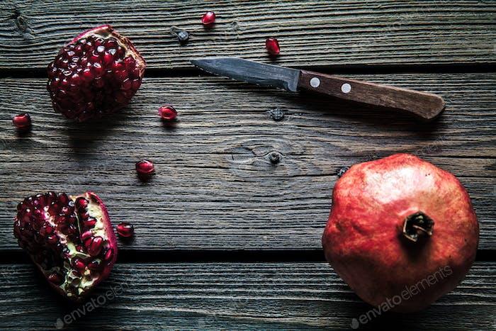 Fresh pomegranates on a wooden background. Organics, fruit, food