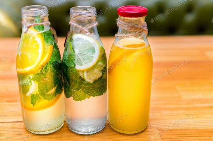 Set of bottles with lemonade or mojito cocktail with lemon and mint
