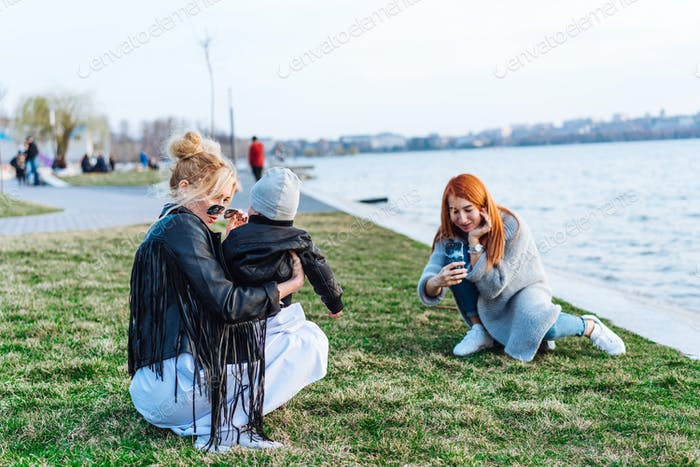 Two women and a little boy on the lake
