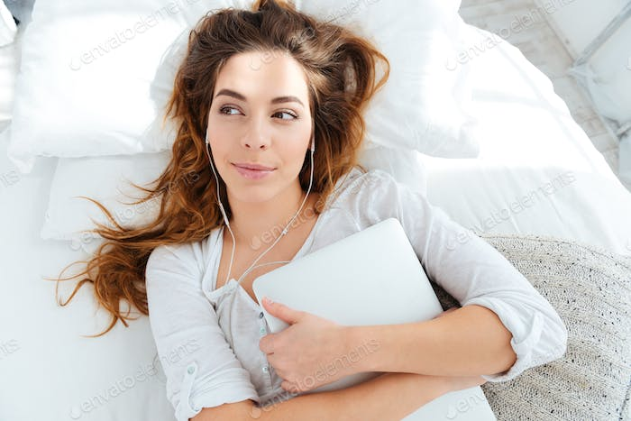 Woman listening music in earphones on the bed