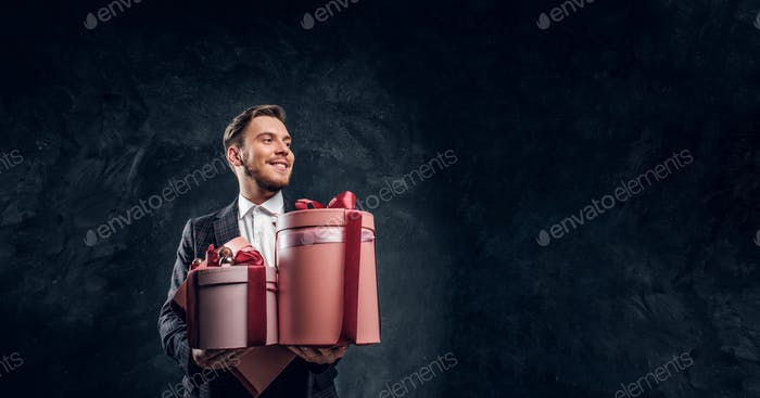 Elegantly dressed man holding gifts while posing in a dark studio