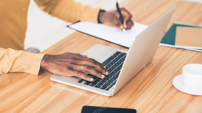 Unrecognizable black guy working on his laptop and writing