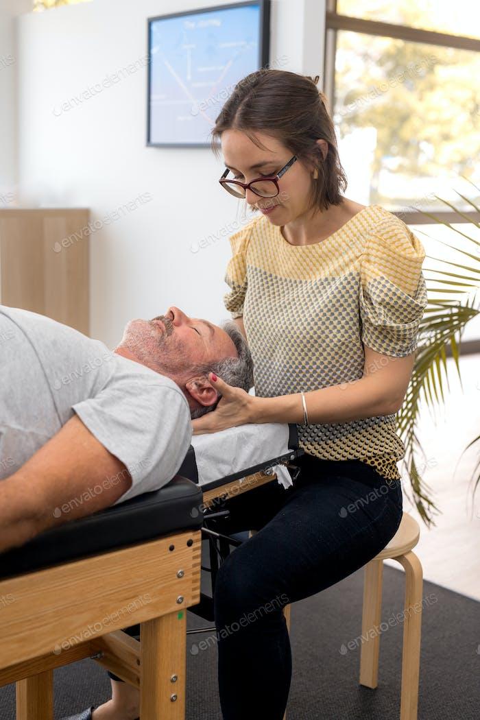 Senior man having chiropractic adjustment