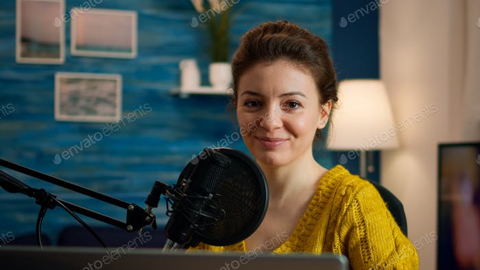 Social media influencer smiling at camera sitting in home studio